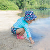 A young girl standing on the bank reaching toward the water while wearing the navy flamingo Bucket Sun Protection Hat.