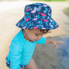 A focused camera shot of the navy flamingo Bucket Sun Protection Hat on dark curly haired girl wearing an aqua shirt.