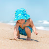 A cute toddler squatting and digging in the sand while wearing the Aqua Dinosaurs Bucket Sun Protection Hat and matching trunks.