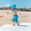 A toddler running through the waves on the beach while wearing the Aqua Dinosaurs Bucket Sun Protection Hat and matching trunks.