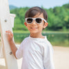 An young boy with an adorably forced smile posing with his arm on a lifeguard pole with some white Flexible Sunglasses on.