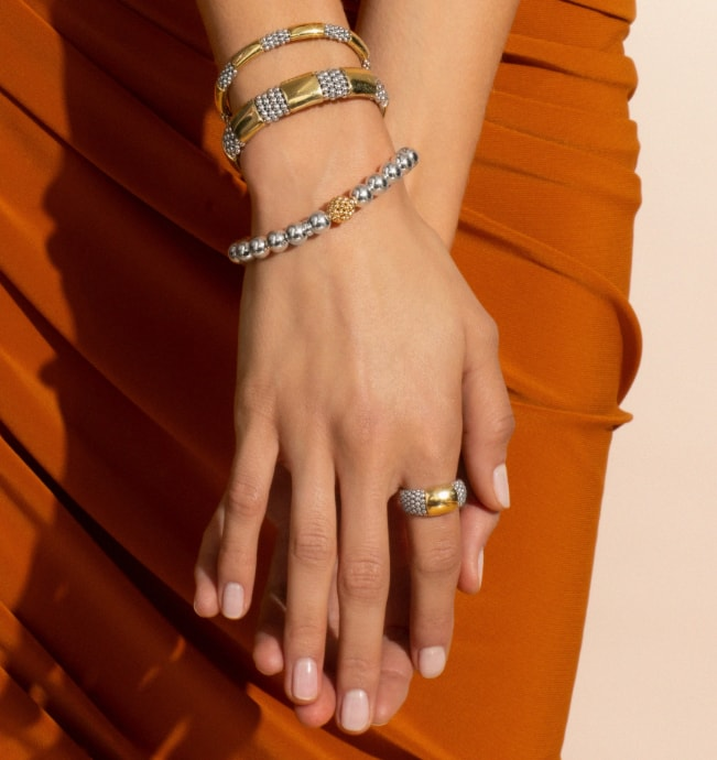 model shows High Bar gold and silver bracelets and rings against her ochre colored skirt