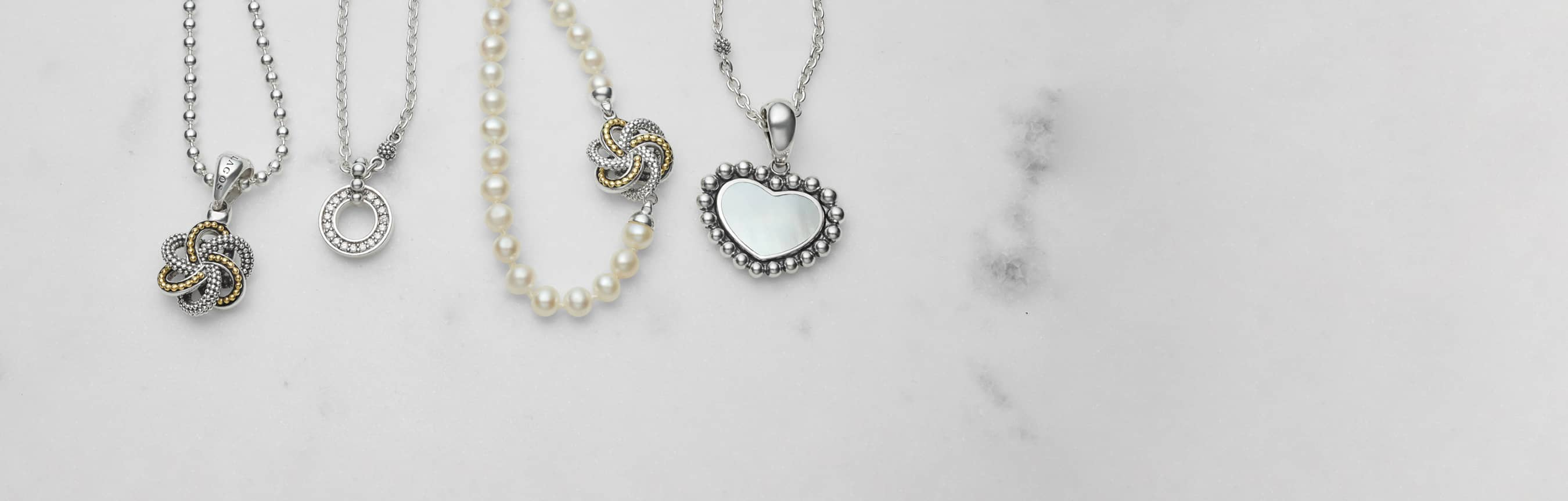Pearl, Mother of Pearl, diamond and gold and silver love pendant necklaces displayed in a row.