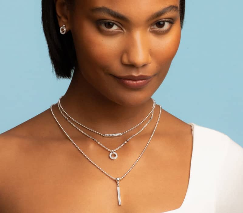 African-American model wearing Caviar Spark diamond earrings and diamond station necklaces and diamond pendant necklaces.