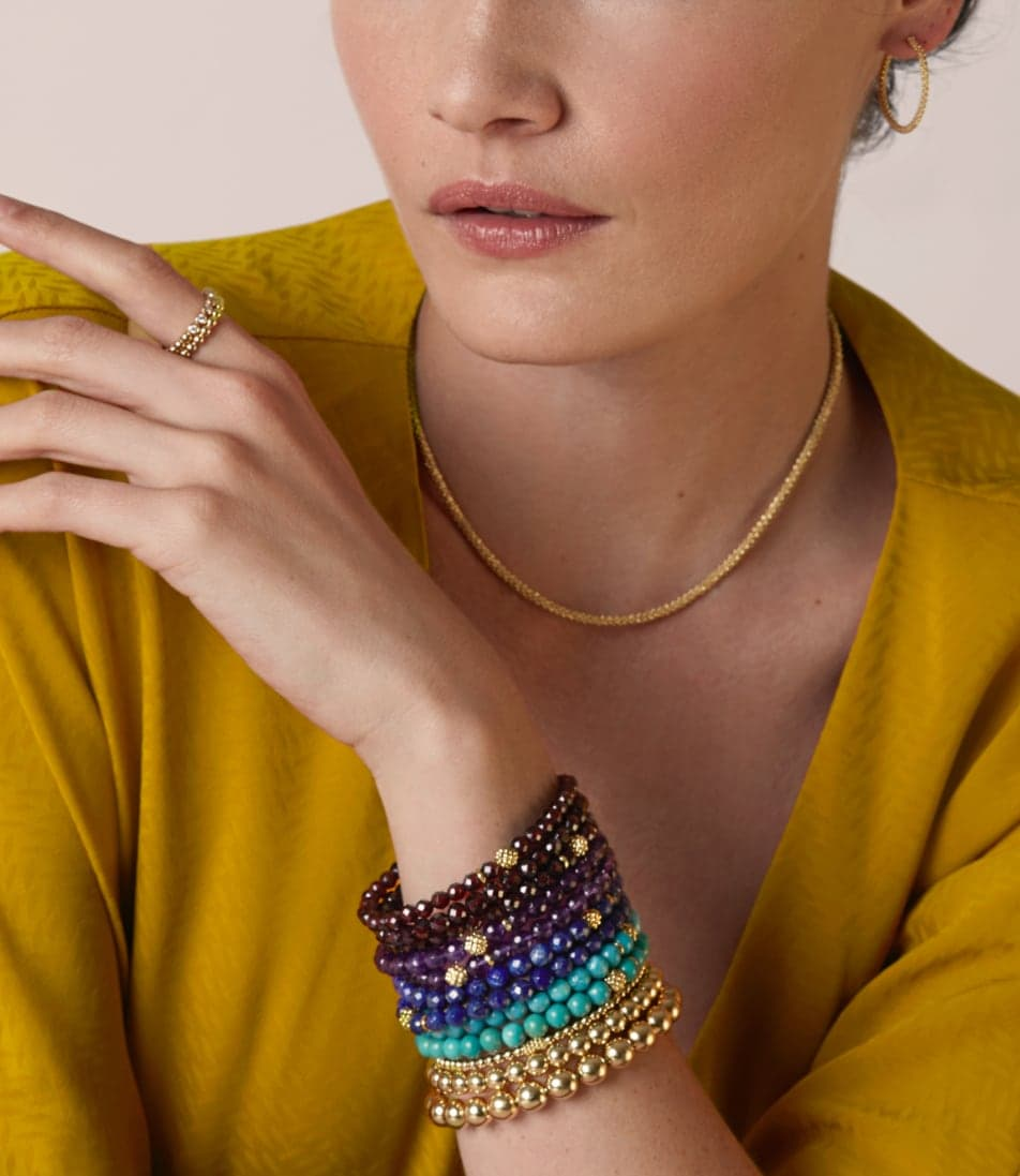 Feminine model with ochre blouse wearing gold hoop earrings and necklace. On her wrist is a stack of gemstone and gold Caviar braclets.