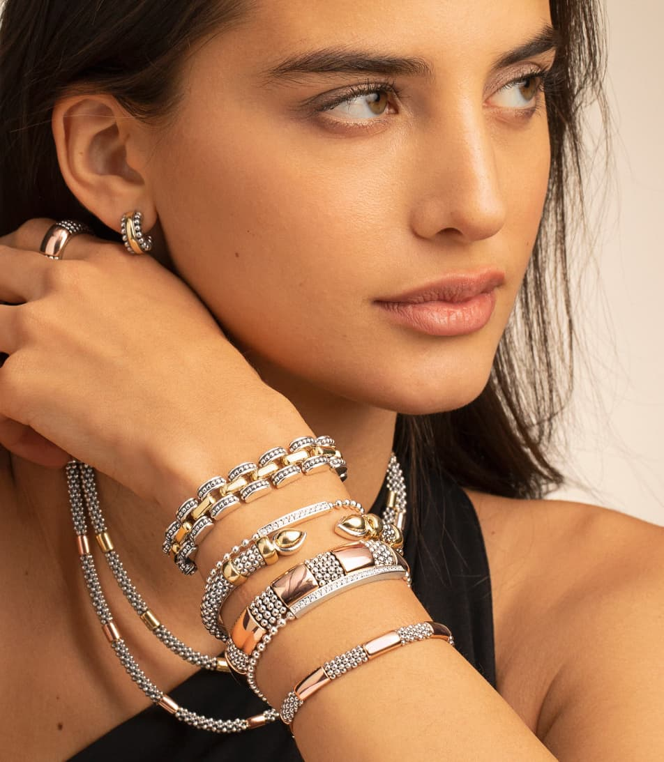 Feminine model wearing gold hoop earrings and necklace. On her wrist is a stack of two tone silver and gold Caviar braclets.