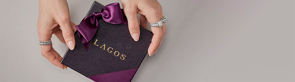 Feminine hands wearing Caviar Spark diammond rings holding the Iconic LAGOS gift boxes