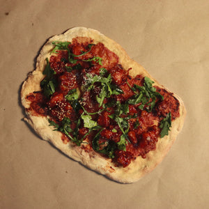 hand pulled thin crust pizza with korean honey garlic fried cicken, arugula and parmesan