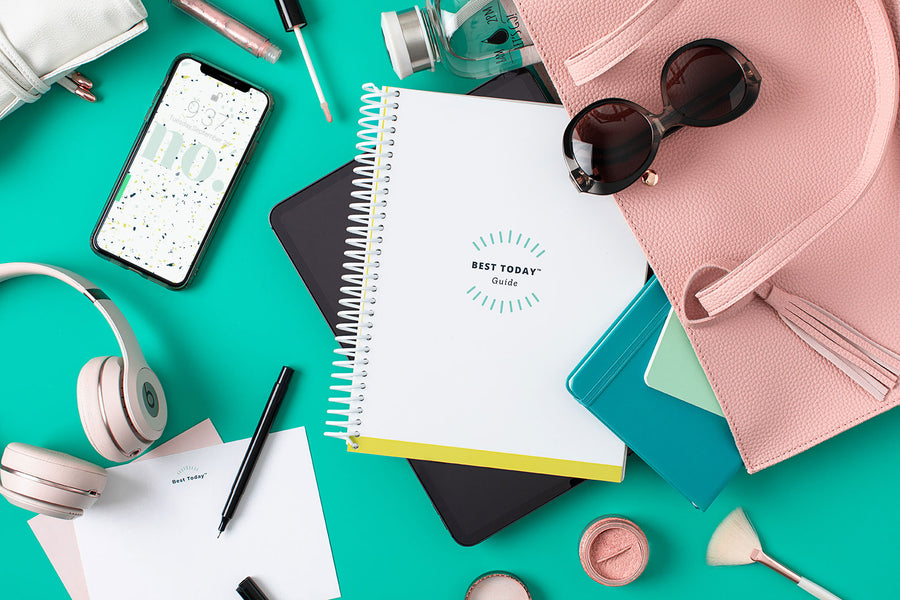 "Iphone with the ""No"" teal, blue and lime green confetti wallpaper/screensaver. Best Today Guide popping out of a pink large day bag along with blush pink headphones, Best Today notepad, pen, makeup and glasses."