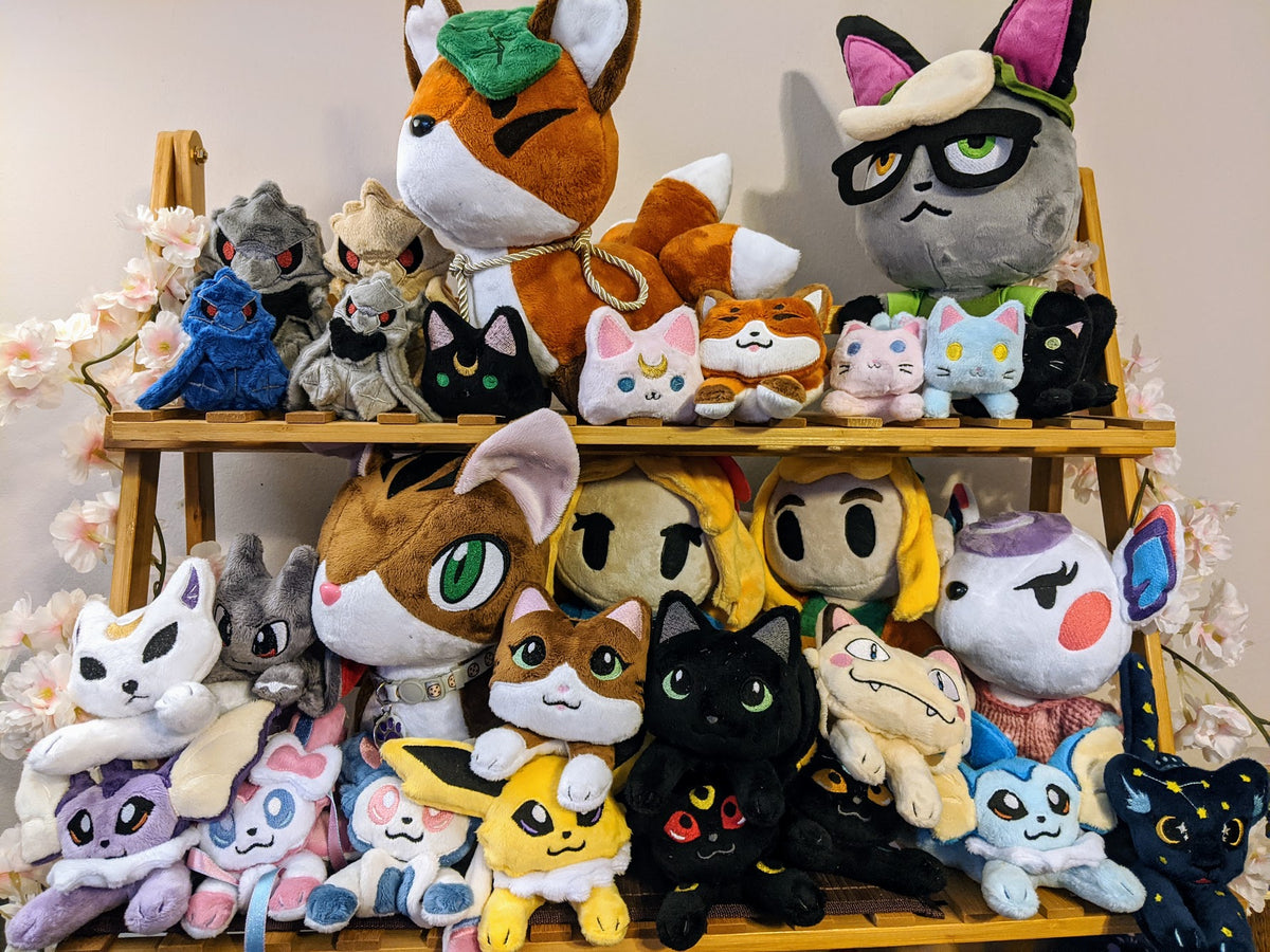 A collection of various plush made by Moonkitty on a bamboo shelf decorated with cherry blossoms.