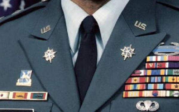 U.S. Army Military Intelligence Branch Insignia pins on service uniform.