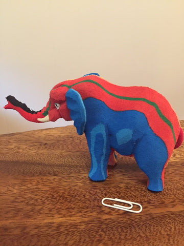 Small elephant pictured with paperclip for scale