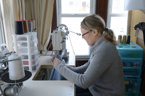 Jennifer Couch sewing a recycled bag on a cylinder arm sewing machine