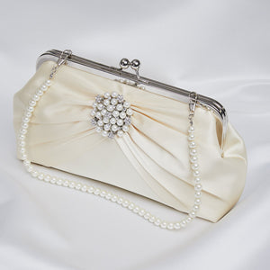 Keep all your essentials together in this beautiful cream satin bag. Cream glass beads and diamantes make centre stage along with a timeless cream handle.  Matching earrings, hairclips, necklace and bracelet available.  Pearl handle. 40cm 26cm x 6cm x 14cm.