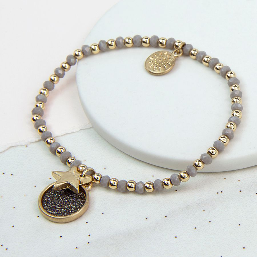 A wonderful stretch bracelet with grey and gold plated beads. We love the combination of the star charm and grey sparkle disc in a worn finish.     Approx disc size 13mm, approx star size 10mm.