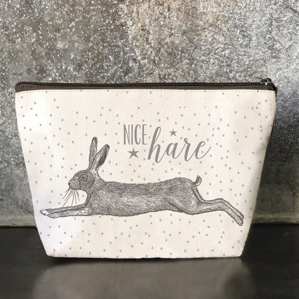"This beautiful canvas toiletry / cosmetic bag is a great way to store all your lovely things. It has a picture of a cute hare with the words ""Nice Hare"" on the front and the back. The body of the bag is beige with blue polka dots all over. It fasens with a with a black zip and metal pull and is lined with black waxed cotton.    Size - 25 x 15.5 x 0.7cm."