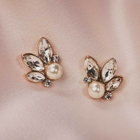 Grace Kelly was frequently pictured wearing pearls and so pearls were raised to iconic status during the 1950's.  These striking Pearl and Leaf Stud Earrings have been handpicked for their Authentic Vintage inspired design and we think Grace would certainly approve.  Matching necklace also available.   Hypoallergenic and Nickel free. Length - 1.5cm Width - 1.5cm.  Colour - Cream Glass Pearl.  Brass plating.