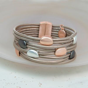 Creating a layered look, this stylish bracelet has multiple strands of taupe coated leather which are fastened together with a rose gold style magnetic clasp.  A selection of metallic beads are threaded onto two strands at a time in dark grey, silver and rose gold finishes. Each bead has a matt finish brining an understated, contemporary feel to the design.