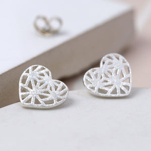 We adore these hand crafted heart earrings which bring texture, style and romance together in one design.  Using fine quality sterling silver and traditional craftsmanship, these beautiful heart stud earrings have a solid outline and the centre is filled with intricate lattice work. The surface has been given a fine scratched finish, which adds a contemporary tactile element.   Size - 10mm.
