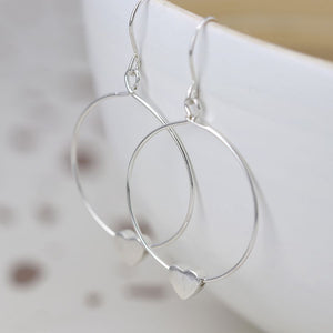 These fine hoop earrings have been hand crafted from sterling silver and suspended from silver earring hooks. Each hoop has a chic subtle worn finish and features a sliding silver heart which is threaded onto the hoop allowing them to swing and move freely.     Size - hoop 25mm, heart 6mm.