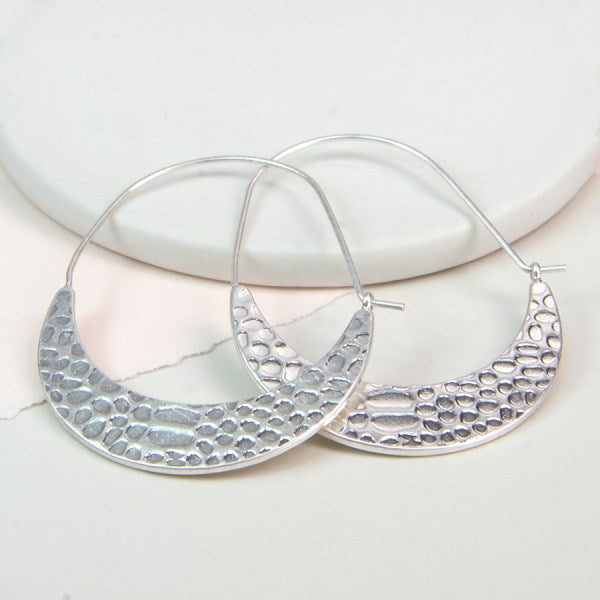 These lovely earrings feature two large crescent shapes plated in a layer of real silver and given a subtle matt finish. The surface of each crescent is textured to create little oval indents. Fine silver plated earring wires are attached to the tip of each crescent and are hooked through a small loop on the other end. We love the curved shape of these earrings and they would finish any look off beautifully.  Size - width 37mm, length 50mm