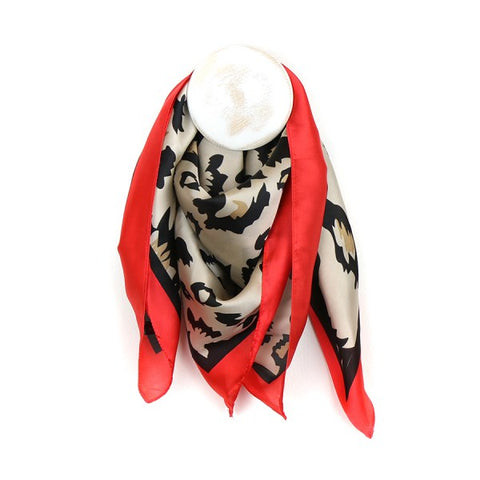 With the feel of silk, this eye catching square polyester scarf features an oversize graphic leopard print in caramel, ecru and black. Edged with a vibrant red boarder and fine black strip, the combination of neutral shades and bold splash of colour make it the perfect addition for any wardrobe.  Size - approx. 70cm x 70cm