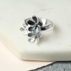 This silver plated stretch ring looks great on and looks just like a solid silver ring! It has three different size flowers in various shades of grey enamel. Perfect for day to evening wear this Spring / Summer.