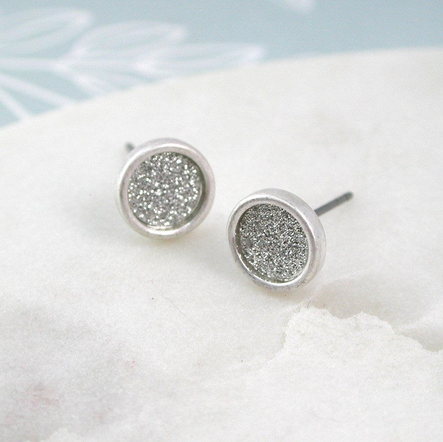 We love the shimmering glitter finish on these round disc stud earrings which make them suitable for any occasion. The outer edges are raised and the silver plating is given a worn finish. If you love a hint of sparkle in a contemporary and understated style, these glitter stud earrings are ideal.   Size 8mm.