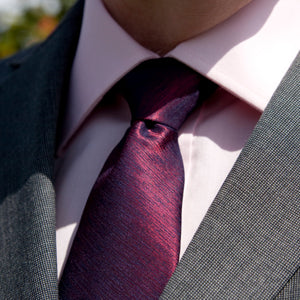 A solid light pink shirt with a solid purple tie