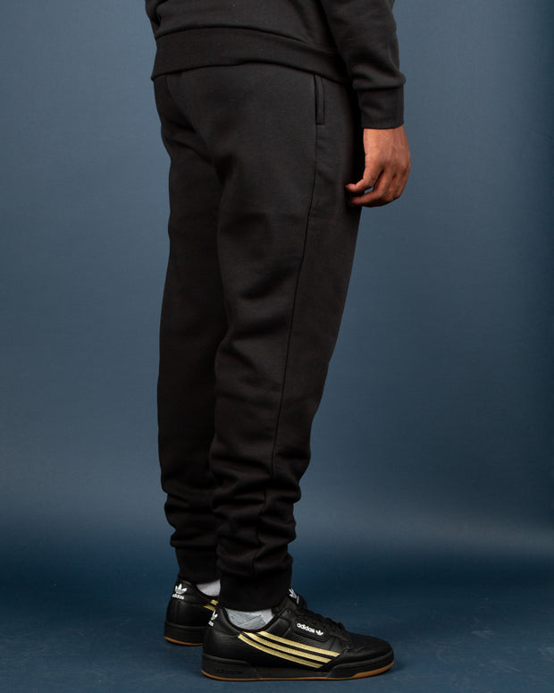 Bringing OG Adidas style to your winter wardrobe with the Adidas Originals 3D Trefoil Graphic Sweatpant in black. Constructed from a warm and cosy cotton blend that is 30% recycled, these black track pants feature a 3D Trefoil logo embroidered in white on the front left pocket and are signed off with a comfortable drawcord elasticated waistband.