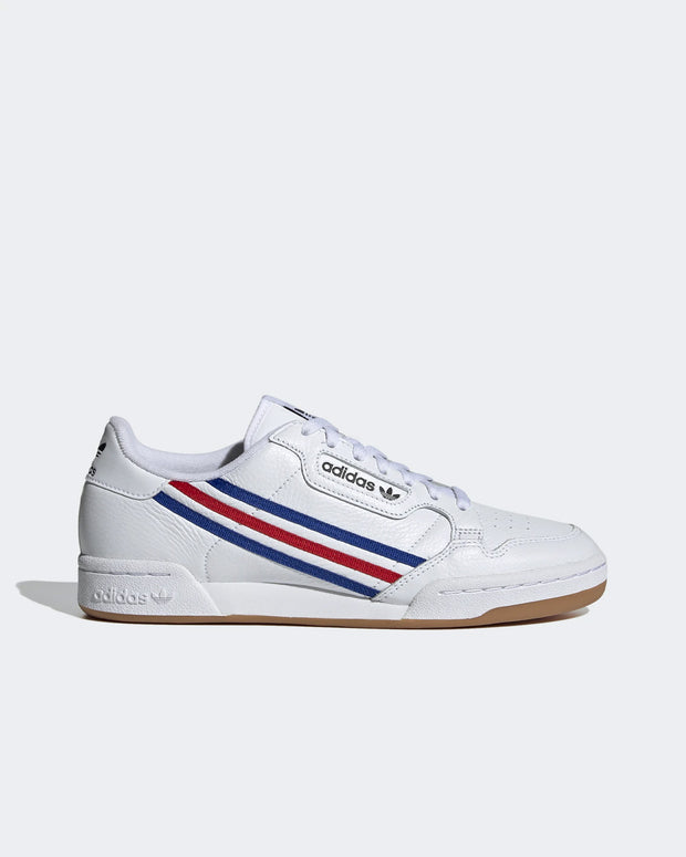 An 80's tennis sneaker, refined with modern technology and style. The Adidas Originals Continental 80 in White/Royal Blue and Vivid Red is a timeless sneaker, constructed with leather uppers and a classic gum rubber outsole. Slip them on with any outfit and you will be rolling, these low profile white sneakers are perfect for every day of the week. Signed off with a comfortable fabricated lining.