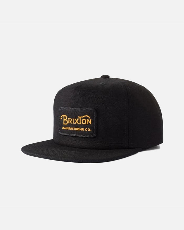 The Brixton Grade HP Snapback Hat in Black is a high profile 5-panel construction, made sturdy from a high-quality canvas. The design features a merrowed-edge embroidered Brixton logo patch on the front with contrasting yellow writing. A laid back simple black cap which is perfect for every day of the week and finished with an adjustable snapback strap.