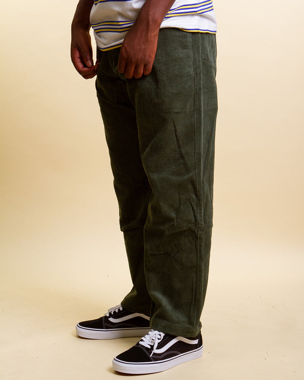 The Butter Goods Digger Corduroy Pants in leaf bring a utilitarian aesthetic mixed with vintage workwear and military. Constructed from high wale corduroy, these pants a loose-fitting and sit perfectly at the ankle. A comfortable silhouette fitted with branded embroidery on the back pocket, silver zip fly, woven label on the side and a clean nylon belt buckle closure to sign off.