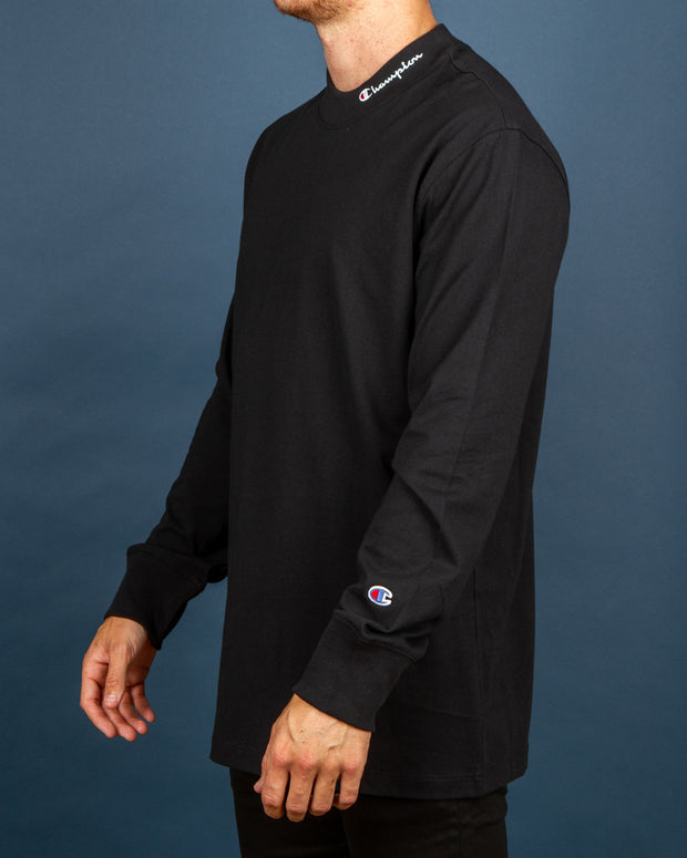 The Champion Mock Neck Longsleeve Tee in black is sure to keep you looking fresh this winter. Built with a slight high neck and long sleeves from a premium cotton jersey, this ultimate layering option is fitted with ribbed trims and a relaxed fit. Signed off with an embroidered Champion logo on the mock neck as well as a 'C' logo on the left sleeve.