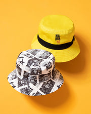 In standard HUF style, the 2 in 1 bucket hat deal. The HUF x Kill Bill Reversible Bucket Hat in yellow is constructed from sturdy cotton twill with a classic short brim silhouette. The exterior features a HUF x Kill Bill logo at the front with a contrasting yellow stripe, while the reverse side offers an all-over print, highlighting iconic scenes from Tarantino's famous movie.