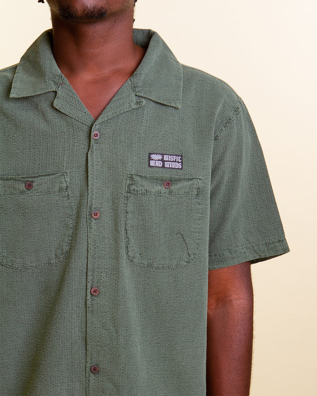 MISFIT bring summer vibes with the Exodust Short-sleeve shirt in Hedge green. Constructed with a relaxed fit, this textured shirt features a collared neckline, button-up front, two patch pocket with buttons and is signed off with a woven MISFIT logo tag at the left chest.