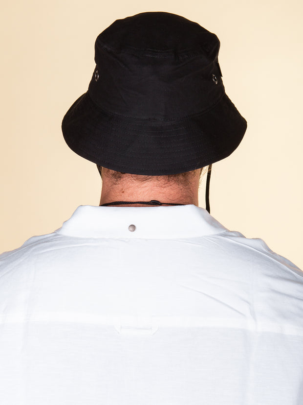 Back view of black RPM bucket hat, medium depth with short brim, stitched on brim, worn with white shirt.