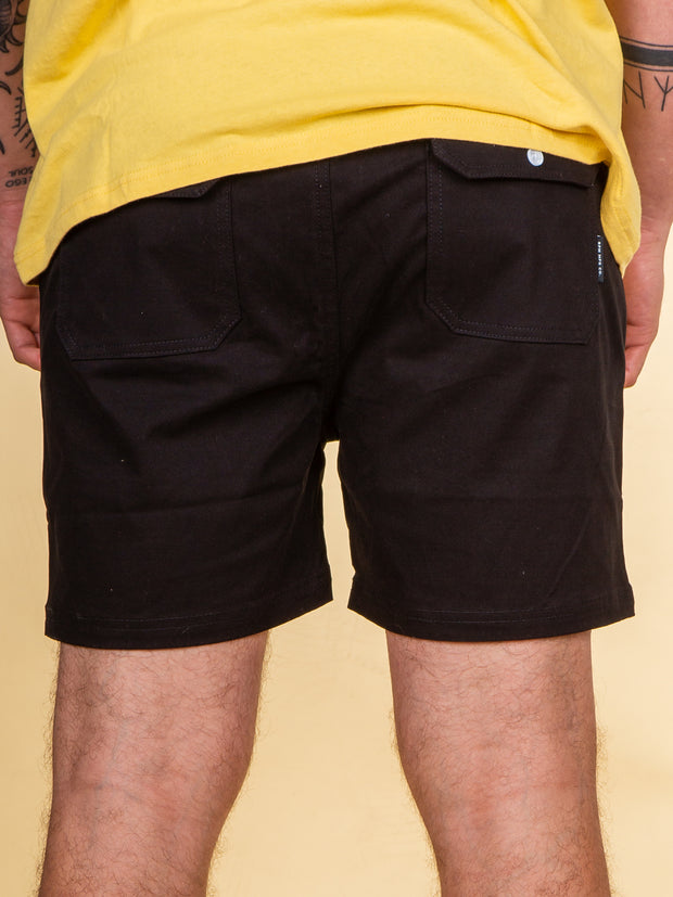 Rear view of the clyde short in black by RPM clothing. pockets on both cheeks with white snap closure plus a small pip tag stitched into the edge of the right side pocket.
