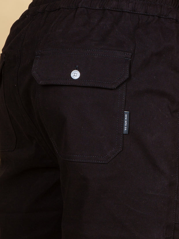 Close up of the rear right pocket, white button closure and grey pip tag on the side. Elasticated waistband is visible at the top of the image.