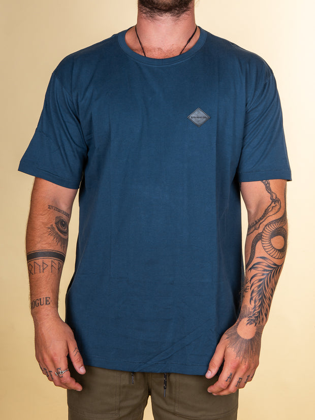 RPM clothing Stitch tee in cobalt blue. Solid Blue colour with small diamond shaped label stitched to the left chest. Label is rubber molded, is 30mm x 30mm and is black in color with embossed negative detailing. It reads RPM MFG CO in capital letters.