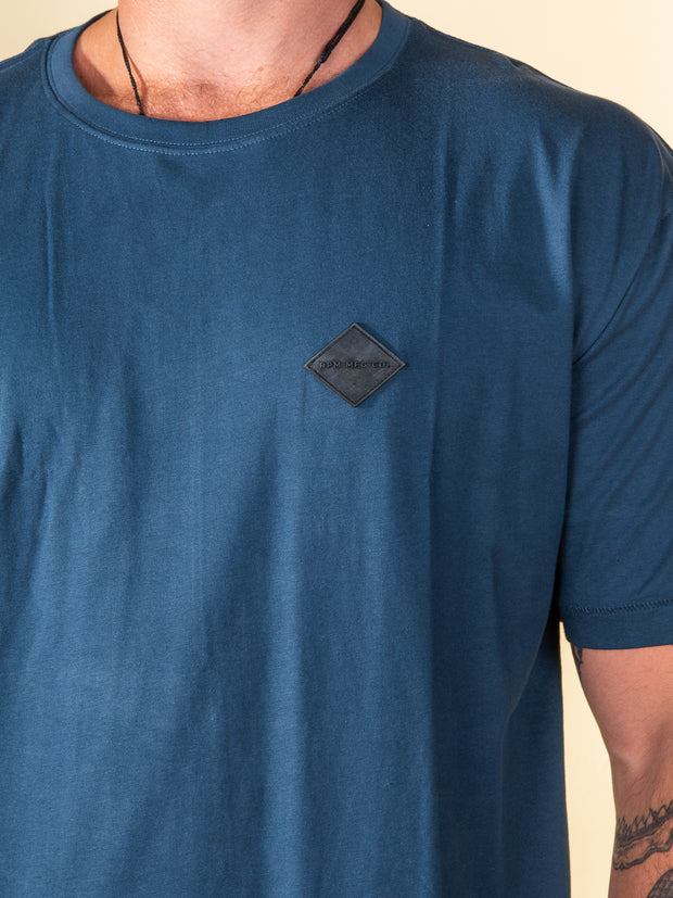Close up view of the rubber label positioned at the left chest of the Stitch tee in cobalt from RPM clothing. The label is 30mm x 30mm and is embossed with negative detail reading RPM MFG CO. in capitals. It is a diamond shaped label.