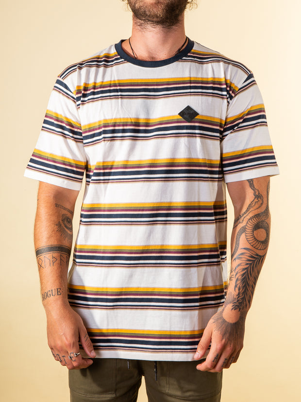 The RPM Stripe tee in multi stripe color. Front view showing the 9 multi colored strips, with rubber label on the left chest. Ringer style neck rib in Navy blue.