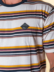 Close up view of the rubber label on the stripe tee in multi color. The label is diamond shaped and solid black with embossed negative detailing.