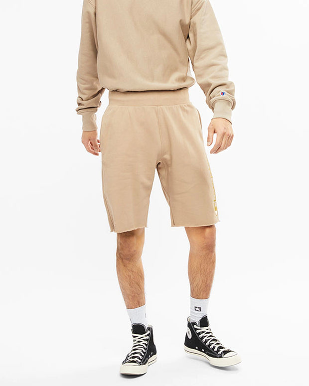 Beige Shorts with a Champion Logo embroidered in yellow text down the left leg. Model wears Converse Chuck 70s Hi and matching Champion Crewneck