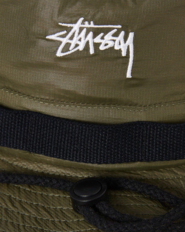 The Stussy Stock Ripstop Boonie in Olive is a laidback styled bucket hat constructed from 100% nylon. This ripstop bucket is perfect for a weekend adventure, complete with webbed strap detailing, an adjustable chin strap, and signed off with an embroidered logo at the front.