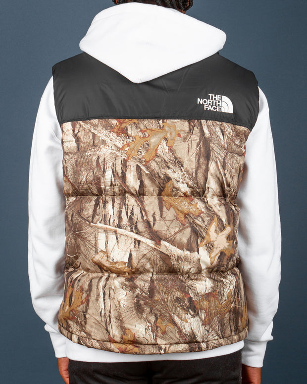 One of the most popular layering options in the winter season, The North Face 1996 Retro Nuptse Vest in Kelp Tan Forest Floor Print. This vest is bound to keep you warm all through winter and will keep you styled for a lifetime. Constructed from premium nylon ripstop with a DWR finish, this vest is filled with down and features a zip closure along with an embroidered TNF Dome logo on the front and back.