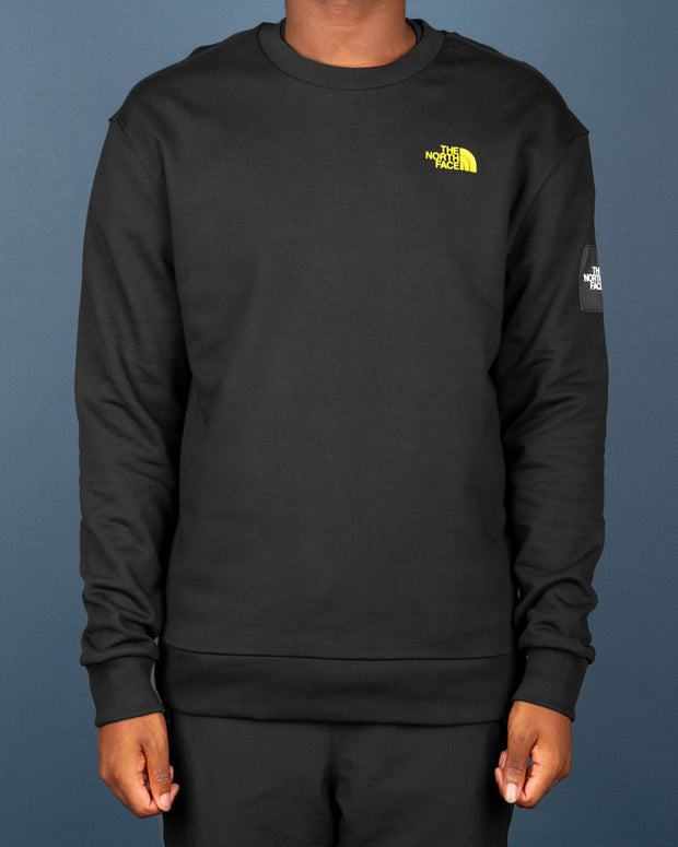 The North Face Black Box Crew Sweat in Black stays authentic to TNF style with a comfortable pure cotton sweater that features a highlighter yellow TNF logo on the front, paired with a custom 'Never Stop Exploring' graphic on the back. Signed off with comfortable ribbed trims, providing perfect everyday comfort.
