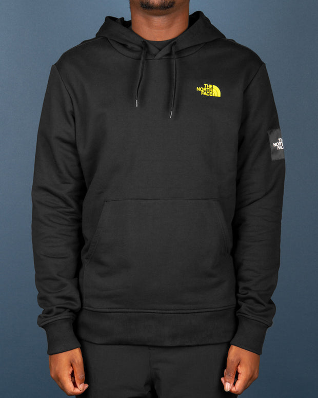 Perfect for winter layering and everyday wear, The North Face Black Box Hoodie in black is styled simply with the iconic TNF logo in highlighter yellow on the front, paired with a custom 'Never Stop Exploring' graphic on the back. Made from pure cotton which is super soft, this pullover hoodie features a drawstring hood and kangaroo pouch pocket, signed off with ribbed trims.