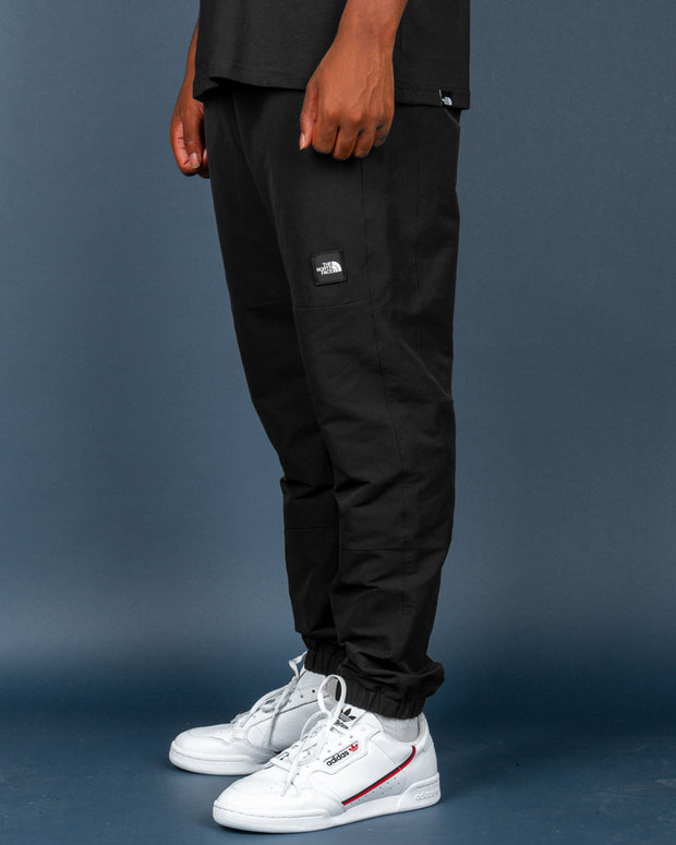From the latest tech range, The North Face brings the best pants to enter your wardrobe, the Black Box Track Pant in Black. Constructed from premium nylon with FlashDry technology, these pants are designed with functionality in mind. Adding to comfort with a slight stretch and secured with an adjustable integrated belt, these pants are signed off with the TNF logo embroidered on the front and back.