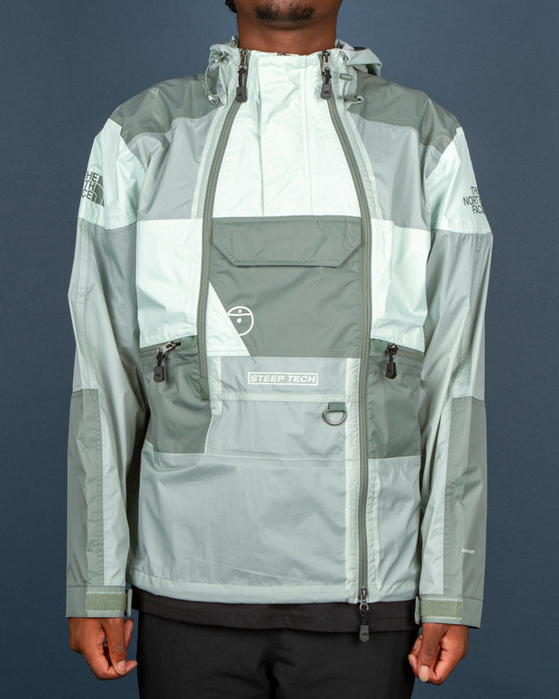 The North Face U Steep Light Rain Jacket in Agave Green is part of their latest tech range. Constructed from nylon ripstop, this lightweight jacket features a panelled colour block in tones of green. Styled with a bungee drawstring hood, two half-zip closures and an offset two-way front zip. Singed off with plenty of pockets for small essentials, D-ring hardware and TNF printed branding all over, this jacket will have you looking your best all through the city.